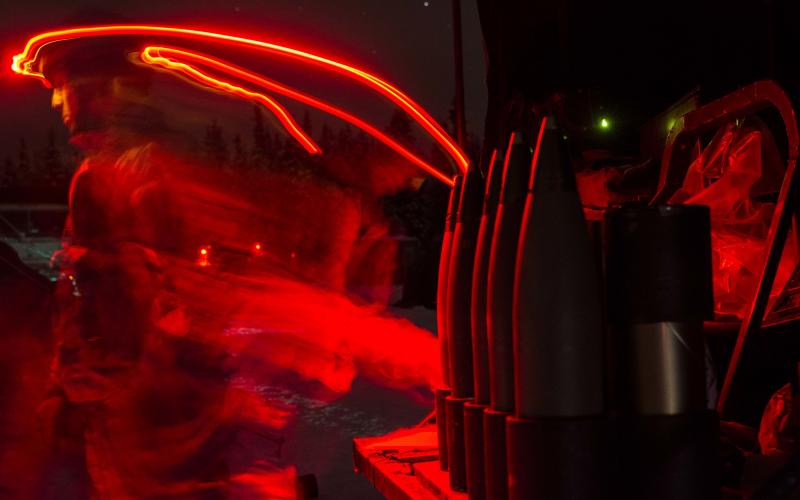 A paratrooper with the 2nd Battalion, 377th Parachute Field Artillery Regiment, 4th Brigade Combat Team (Airborne), 25th Infantry Division, illuminates his area with a red headlamp as he works at a 105 mm howitzer firing point Dec. 10, 2014, at Joint Base Elmendorf-Richardson, Alaska. Paratroopers use the dark, Arctic conditions to gain proficiency in operating in austere environments.