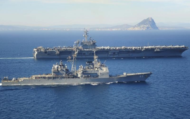 The Ticonderoga-class guided missile cruiser USS Vicksburg, foreground, escorts the Nimitz-class aircraft carrier USS Theodore Roosevelt as they pass the Rock of Gibraltar in the Strait of Gibraltar last March. The Theodore Roosevelt deployed from Norfolk, Virginia, to then make a homeport shift to San Diego at the end of its deployment.