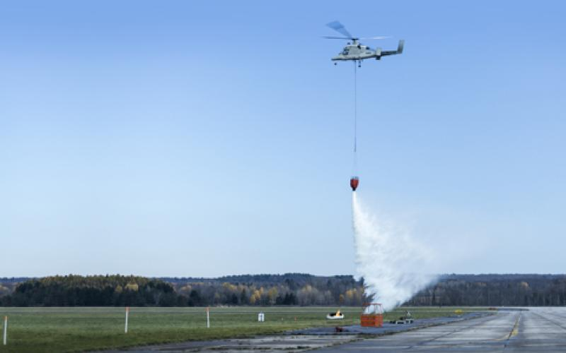 The unmanned version of Kaman Corporation's K-MAX platform demonstrates dropping water on a controlled fire during trials at Griffiss Air Force Base in New York.