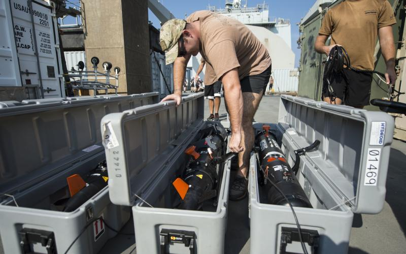 U.S. sailors from EODMU 1 perform preoperational maintenance and checks on their Remus Mk-18 Mod 1 underwater unmanned vehicles as part of a bilateral mine countermeasure exercise involving U.S. and U.K. troops.