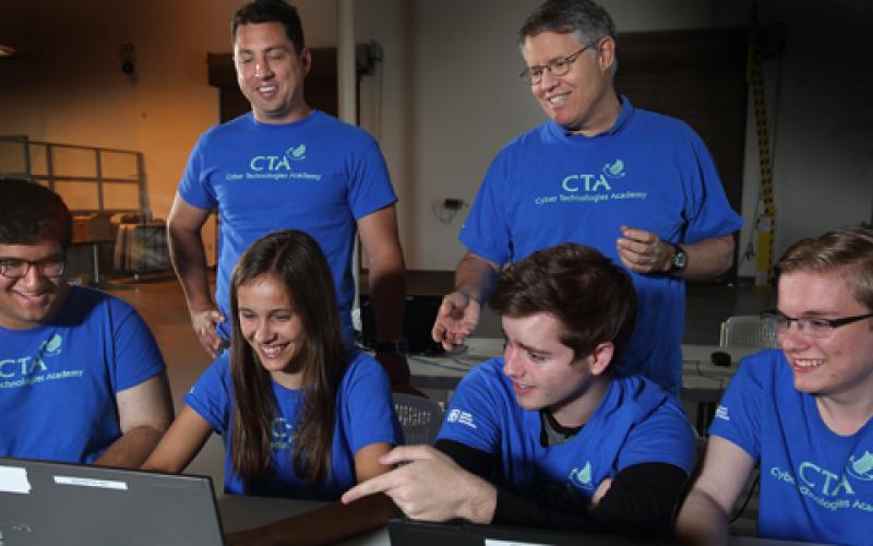 Led by Sandia National Laboratories instructors (top row, from l) C.W. Perr and Steve Hurd, students (bottom row, from l) Anuj Kak, Samantha MacIlwaine, Makena Harmon and Evan Laufer participate in hands-on training exercises as part of Sandia's annual summer Cyber Technologies Academy.