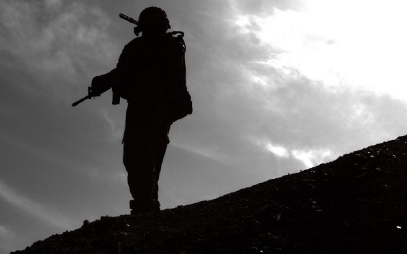 A U.S. Army soldier with the 101st Airborne Division (Air Assault) pauses before ascending a ridgeline near the Afghan village of Kote Khel.