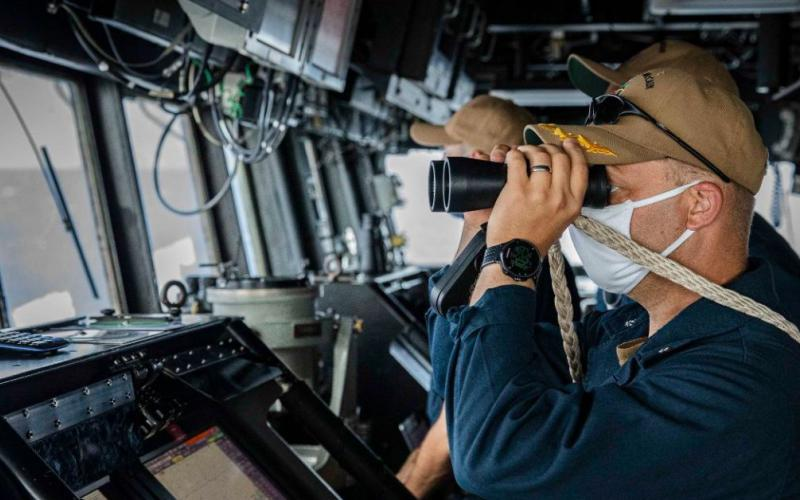 A sailor keeps watch aboard the USS John S. McCain as the guided missile destroyer asserts navigational rights and freedoms under international law in the South China Sea near the Spratly Islands. The U.S. Indo-Pacific Command (INDOPACOM) routinely conducts freedom of navigation operations as part of its mission to ensure free and secure passage in the vast region.  7th Fleet