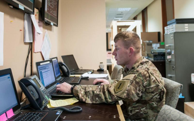 A network operations battle noncommissioned officer with the DHHB, 1st Infantry Division, monitors the CJFLCC-I network near the command's operations center in Iraq. The network employs both Iraqi and U.S. communications capabilities to link diverse forces, along with surveillance and reconnaissance assets, over the country's rugged terrain.