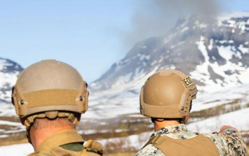A U.S. Marine explosive ordnance disposal technician with Marine Rotational Force-Europe 20.2, Marine Forces Europe and Africa (l) and a Norwegian soldier (r) overlook an explosion of safely detonated high-explosives found during a sweep in Setermoen, Norway, in June.  USMC photo by Lance Cpl. Chase Drayer