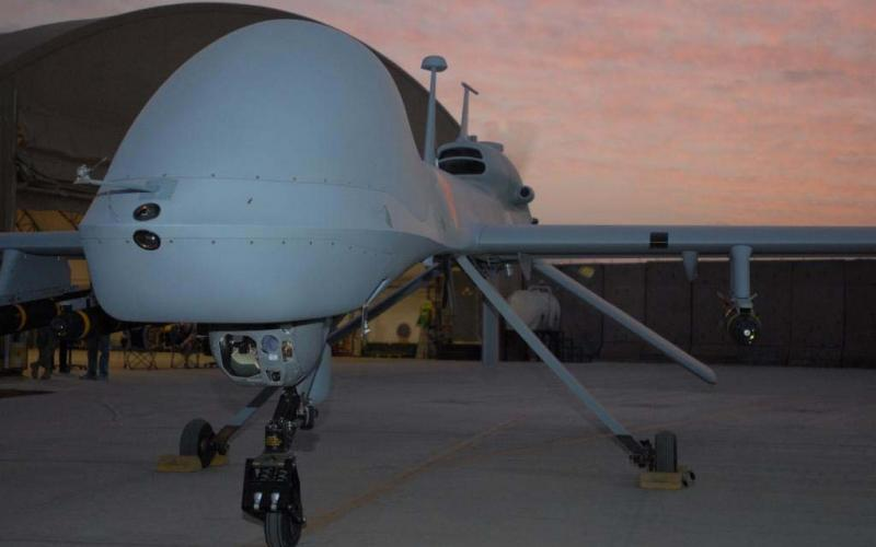 An MQ-1C Gray Eagle armed with Hellfire missiles revs up before taking flight at Camp Taji, Iraq, in 2011.