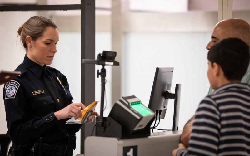 A Customs and Border Protection officer examines travel documents of arriving foreign visitors. All visitors applying for entry to the United States under the Visa Waiver Program are vetted through the National Vetting Center.  Customs and Border Protection