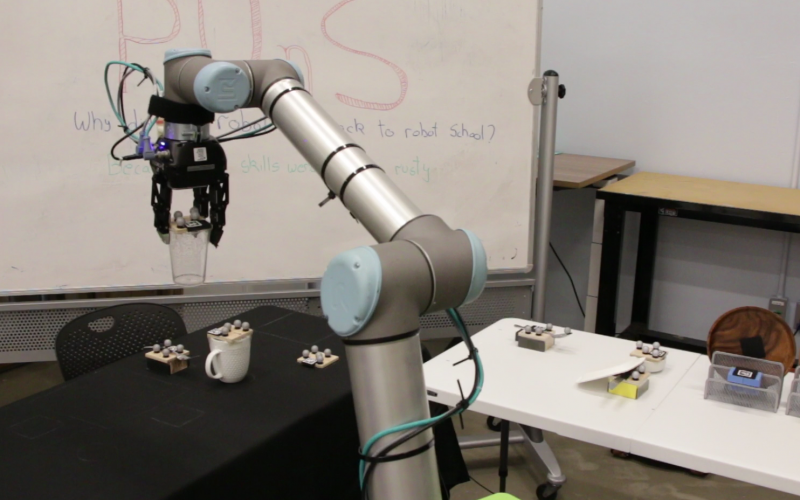 Researchers use markers to aid the robotic arm. The metallic spheres are retro-reflective markers used with the motion capture system, and the scanner codes are fiducial markers that help the system determine the position and orientation of objects.  MIT Interactive Robotics Group