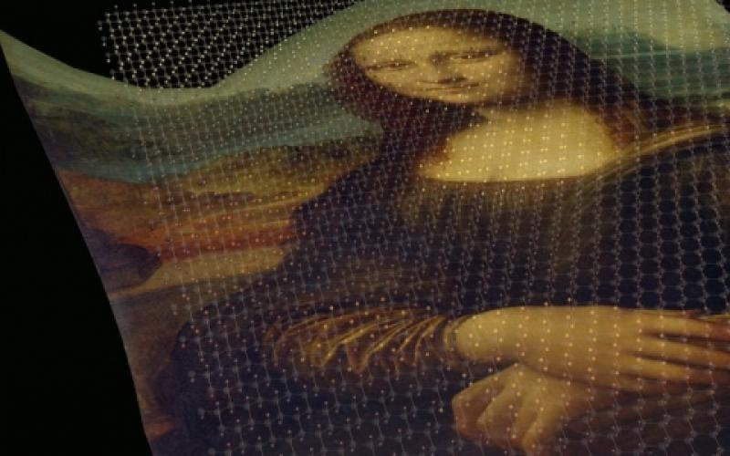 """Picturing graphene as a canvas, researchers are painting the honeycomb structure with hydrogen to confer magnetic and semiconducting capabilities onto the single-atom-thick material—as illustrated in this concept featuring """"Mona Lisa."""""""