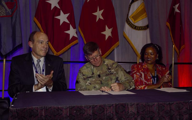 Gen. Fogarty (c) signs the paperwork to initiate a new civilian cyber career program. Ronald W. Pontius, deputy to the commanding general, U.S. Army Cyber Command, and Andricka Thomas, CP-71 director, join him during the signing. Photo by Michael Carpenter