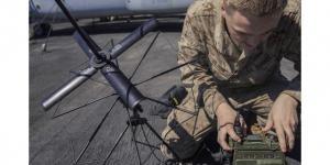 """A U.S. Marine Corps Lance Corporal is assembling an AN/PRC-117G radio on the flight deck of an amphibious assault ship. The Mobile User Objective System (MUOS) adds updated firmware to the radio, giving warfighters more advanced satellite communications."""" Credit: U.S. Marine Corps photo by Lance Cpl. Tawanya Norwood."""