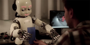 The iCub humanoid robot at IDSIA's robotics lab in Switzerland tries to reach for a blue cup.