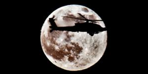 An AH-64D Apache attack helicopter departs the flightline under a full moon to conduct operations from Camp Taji, Iraq. Boeing has received a contract for an additional Longbow crew trainer.
