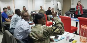 Maj. Nadine Quashie, USA, prepares to ask a question during a breakout session at a contracting symposium the 408th Contracting Support Brigade hosted at Camp Arifjan, Kuwait. Credit: U.S. Army photo by Staff Sgt. Robert Waters, USA
