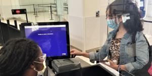 A traveler inserts her driver's license into a new credential authentication technology unit at BWI Airport. In response to COVID-19, the TSA has purchased and continues to contract for innovative technologies that protect its personnel and data as well as travelers. Credit: Photo courtesy of TSA