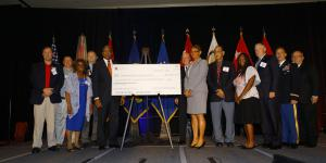 The National Math and Science Initiative presents a check for $455,217 to the schools of Richmond County, Georgia, during the AFCEA TechNet Augusta conference. Photo by Michael Carpenter