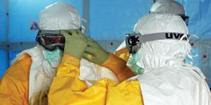 Health care providers adjust personal protective equipment as they prepare to enter a facility treating the Ebola virus in Liberia. Future pandemics could come from natural viruses or biological weapons developed by sophisticated nations; but whichever the source, opportunistic foes will take advantage of their effects to wreak further havoc on victim nations. (U.S. Army photo)