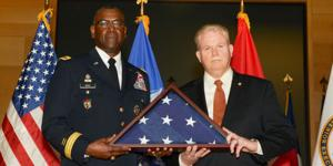 Maj. Gen. Cedric Wins, USA, commander of U.S. Army Research, Development and Engineering Command, presents a flag to Henry Muller Jr., who has retired as director of the Communications-Electronics Research, Development and Engineering Center after a nearly 33-year federal career. Donald Reago Jr. is serving as acting director.