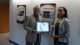 Mansur Hasib, chair of the graduate cybersecurity technology program at the University of Maryland, Baltimore County, presents the 2015 AFCEA STEM Major Scholarship for Diversity Students to Kiara Jones, a graduate.