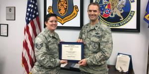 Staff Sgt. Jenna Saenz, USAF, American Military University (l), receives a 2017 War Veterans Scholarship from her commanding officer, Lt. Col. Jonathan Dietrich, USAF, 661st Aeronautical Systems Squadron.