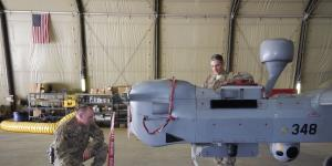 Two U.S. Navy officers inspect an MQ-5B Hunter unmanned aerial vehicle (UAV) at Kandahar Airfield in Afghanistan. The Navy's increased use of UAVs is changing the nature of its air operations, but it also is raising concerns about manned versus unmanned missions.
