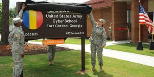 Maj. Gen. LaWarren Patterson, USA, the U.S. Army Cyber Center of Excellence and Fort Gordon commander, and Col. Jennifer Buckner, USA, Army Cyber School commandant, unveil a sign during a ribbon-cutting ceremony for the school.