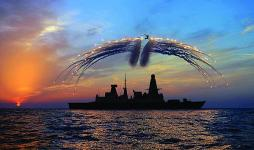 HMS Dragon's Lynx helicopter fires infrared flares during an exercise over the Type 45 destroyer.