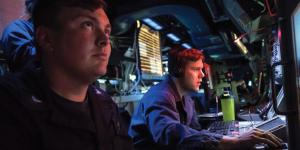 Two U.S. Navy sailors monitor data onboard the USS Jason Dunham during a 6th Fleet area operation. The Naval Information Forces command is consolidating information warfare activities and training to standardize all aspects of the domain across the Navy. U.S. Navy photo