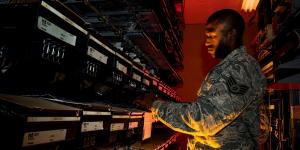 A U.S. Air Force cyber transport systems technician works on an electronic equipment rack at Joint Base Charleston, South Carolina. In addition to traditional cyberthreats, the Air Force is seeing increased cyber activity aimed at bringing down its critical infrastructure at bases in the United States.