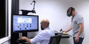 Andrew Sweeney, seated, and another industrial designer with Battelle's Human Centric Design group use virtual reality technology to get user feedback about a hand-held medical device.