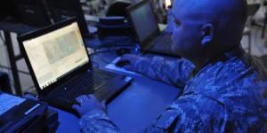 An Army electromagnetic spectrum manager uses a joint spectrum-management planning tool to track mission progress in the field from inside the headquarters tactical operations center as part of Network Integration Evaluation (NIE) in 2014.