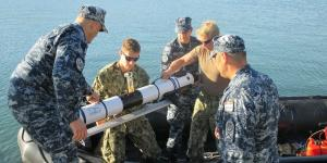 Croatian divers and U.S. sailors with Explosive Ordnance Disposal Mobile Unit (EODMU) 8 load an Iver 3 autonomous underwater vehicle (AUV) into the MK-5 Zodiac for testing.