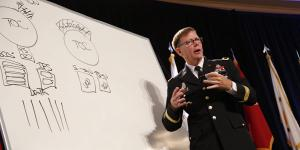 Maj. Gen. Stephen Fogarty, USA, commanding general of the U.S. Army Cyber Center of Excellence at Fort Gordon, Georgia, takes to the whiteboard to illustrate dysfunctional stovepipes that keep military disciplines from sharing information and missions.