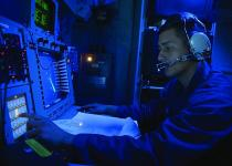 A U.S. Navy cryptologic technician monitors the electromagnetic spectrum of air and surface contacts in the combat information center aboard the guided-missile destroyer USS Ramage.