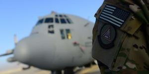 An airman from the 41st Expeditionary Electronic Combat Squadron stands next to an EC-130H Compass Call aircraft in September 2014 at Bagram Air Base, Afghanistan. The squadron provides counter-communications electronic attack capabilities.