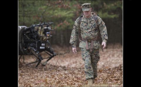 Brig. General Kevin Killea, USMC, Marine Corps Warfighting Laboratory commanding general, leads the Legged Squad Support System through the woods at Fort Devens, Mass. Wearing a special pack fitted with thick black bands that the robot is programmed to identify and track, the general led LS3 through the woods over uneven and sometimes tricky terrain.
