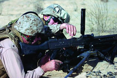 A U.S. Marine Corps sergeant shows then-Rear Adm. Kendall Card, USN, commander, Expeditionary Strike Group 3, how to load the M-240B machine gun during Adm. Card's visit with the 26th Marine Expeditionary Unit during a 2008 training exercise.