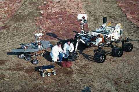 Three generations of Mars rovers developed at NASA's Jet Propulsion Laboratory in California pose with spacecraft engineers at JPL's Mars Yard testing area.   (photo credit: NASA JPL-Caltech)