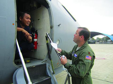 A C-130 pilot with the North Carolina Air National Guard speaks with an airman from the Royal Malaysian Air Force prior to the first flights of Pacific Airlift Rally 2013. The event is a biennial, military airlift symposium sponsored by U.S. Pacific Air Forces for nations in the Indo-Pacific region.