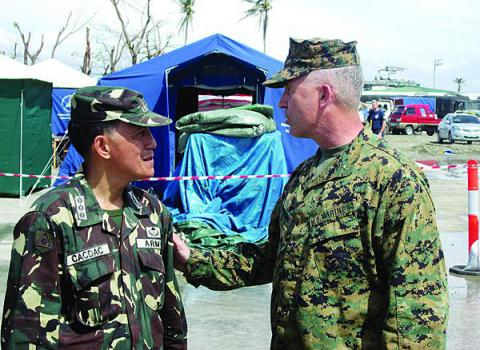 Brig. Gen. Paul Kennedy, USMC (r), commanding general of the 3rd Marine Expeditionary Brigade, discusses Operation Damayan logistics with Col. Emmanuel Cacdac, PA, at Tacloban airport. Strong organizational and personal links established over the course of extensive multinational and bilateral exercises were vital to effective interoperability during the operation.