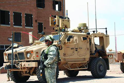 A soldier stands next to a WIN–T Increment 2 point of presence vehicle during its initial operational test and evaluation concurrent with the Army's Network Integration Evaluation (NIE) 12.2 at White Sands Missile Range, New Mexico. Ongoing NIE tests could help clear the way for a full-rate production decision for Increment 2 later this year.