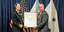 DISA Director Vice Adm. Nancy A. Norton, USN, presents Steve Wallace with his promotion certificate as he takes over the agency's newly created Emerging Technology (EM) Directorate.