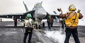 Aboard the USS Carl Vinson in the East Sea in 2017, sailors help ready an EA-18G Growler for catapult launch. The U.S. Navy is evolving its airborne electronic warfare capabilities, replacing the 40-year old ALQ-99 system on the Growler with Next Generation Jammer (NGJ) technologies covering low-, mid-, and high-bands. It tapped Raytheon to work on a mid-band NGJ pod for the aircraft. Credit: Navy photo by Petty Officer 2nd Class Sean M. Castellano