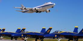 A Boeing E-4B, an airborne command post, flies over the U.S. Navy Blue Angels F-18s during an air show. The E-4B serves as the National Airborne Operations Center for the president and secretary of defense. In case of national emergency or destruction of ground command control centers, the E-4B provides a survivable, command, control and communications center to direct U.S. forces, execute emergency war orders and coordinate actions by civil authorities.