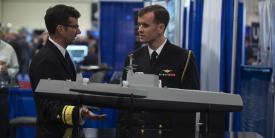 """Rear Adm. Christian """"Boris"""" Becker, USN, commander, SPAWAR (l), discusses naval capabilities with another officer while visiting the Office of Naval Research and Naval Research Laboratory  exhibit at the Navy League's Sea-Air-Space Exposition last year. SPAWAR System Command's recent Other Transaction Agreement (OTA) award for its Information Warfare Research Project  will drive key innovative information warfare capabilities to the Navy, Rear Adm. Becker says. Credit: U.S. Navy photo by John F. Williams"""