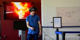 Jack Lewis, a NIST associate, demonstrates the use of a virtual reality headset and controllers with NIST's virtual office environment in which first responders search for a body in a fire. Credit: Burrus/NIST