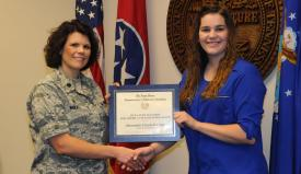 Alexandria Elizabeth Camp of the University of Memphis (r) receives an AFCEA STEM Teachers for America's Future Scholarship from Lt. Col. Kristina M. Whicker of the Tennessee Air National Guard.