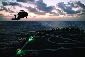 An H-60S helicopter conducts deck landing qualifications on USS Milius destroyer off the coast of Guam. Milius was the first ship to begin installing CANES and will serve as the operational testing platform for the next-generation afloat network.