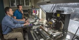 Sandia National Laboratories researchers Jon Ihlefeld (l) and David Scrymgeour use an atomic-force microscope to examine changes in a material's phonon-scattering internal walls, before and after applying a voltage.