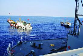"Two Chinese trawlers stop directly in the path of a U.S. Navy ocean surveillance ship in international waters in the South China Sea, forcing the ship to conduct an emergency all-stop to avoid a collision. China employs a broad spectrum of vessels ranging from ""civilian"" fishing boats to armed navy warships to enforce its claims to multiple territories in and around the South China Sea."